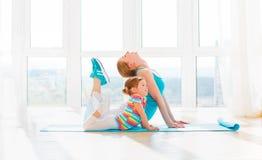 La madre della famiglia e la figlia del bambino sono impegnate nella forma fisica, yoga a Fotografia Stock Libera da Diritti