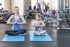 La madre della famiglia e la figlia del bambino sono impegnate nella meditazione e nell'yoga Fotografia Stock