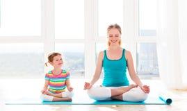 La madre della famiglia e la figlia del bambino sono impegnate nella meditazione ed in y Immagine Stock
