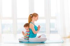 La madre della famiglia e la figlia del bambino sono impegnate nella meditazione ed in y Fotografia Stock Libera da Diritti