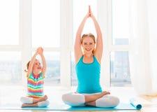 La madre della famiglia e la figlia del bambino sono impegnate nella meditazione ed in y Fotografie Stock