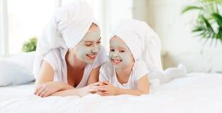La madre della famiglia e la figlia felici del bambino fanno la maschera della pelle del fronte immagini stock