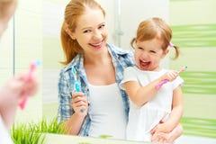 La madre della famiglia e la ragazza felici del bambino pulisce i denti con lo spazzolino da denti Immagini Stock Libere da Diritti