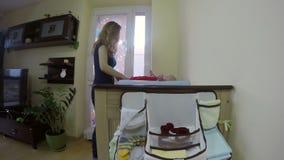 La madre desnuda su paño del cuerpo del bebé en la tabla cambiante del pañal 4K almacen de metraje de vídeo