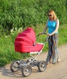 la madre di Quaranta-anno cammina con un carrello di bambino Fotografia Stock