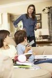 La madre dice i bambini fuori per la sorveglianza della TV mentre facendo il compito Fotografia Stock
