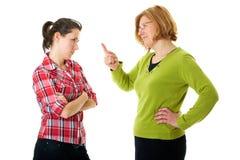 La madre discute con su hija, aislada en blanco Foto de archivo libre de regalías