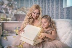 La madre e la figlia aprono un regalo di Natale Fotografia Stock