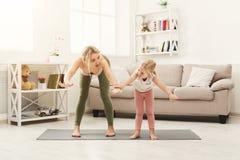 La madre e la figlia che fanno l'yoga si esercita a casa Immagini Stock