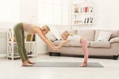 La madre e la figlia che fanno l'yoga si esercita a casa Fotografia Stock Libera da Diritti
