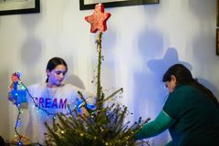 La madre e la figlia decorano l'albero di Natale Immagini Stock