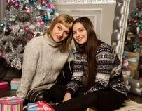 La madre e la figlia felici del teenag vicino all'albero di Natale a casa ridono ed abbracciano fotografia stock