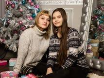 La madre e la figlia felici del teenag vicino all'albero di Natale a casa ridono ed abbracciano fotografia stock libera da diritti