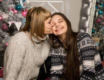 La madre e la figlia felici del teenag vicino all'albero di Natale a casa ridono ed abbracciano fotografie stock libere da diritti