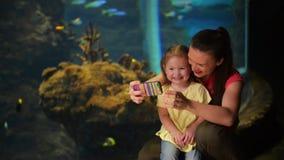 La madre e la figlia felici stanno prendendo Selfie L'acquario con i pesci è su fondo Hanno molto divertimento questo ` s della m stock footage