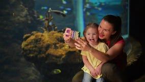 La madre e la figlia felici stanno prendendo Selfie L'acquario con i pesci è su fondo Hanno molto divertimento questo ` s della m video d archivio
