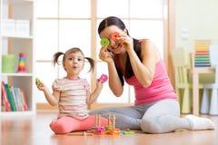 La madre e la figlia giocano sul pavimento che ha un passatempo di divertimento fotografia stock libera da diritti