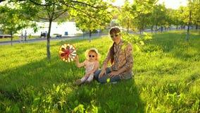 La madre e la figlia passano felicemente il tempo che gioca insieme sull'erba al tramonto video d archivio