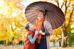 La madre e la figlia sono nel parco della città di autunno La gente sta posando sotto l'ombrello I bambini ed i genitori stanno s fotografia stock