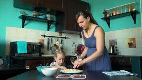 La madre e la figlia spruzzano il formaggio sulla base della pizza video d archivio