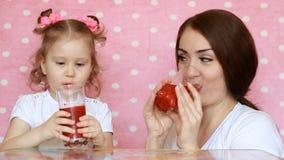 La madre e la figlia stanno bevendo i frullati, sorridenti Giovane donna con il suo bambino che gode di una bevanda saporita di r archivi video