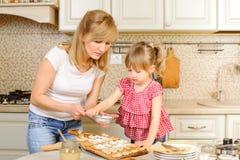 La madre e la figlia stanno cucinando i biscotti Mamma e bambino divertendosi nella cucina Alimento casalingo e piccolo assistent fotografie stock libere da diritti