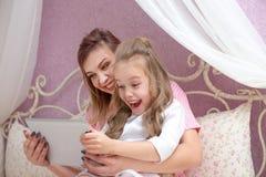La madre e la figlia stanno utilizzando un computer della compressa fotografia stock libera da diritti