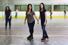 La madre e la figlia alla pista di pattinaggio di pattinaggio a rotelle mettono a fuoco sulla mamma immagine stock libera da diritti