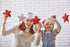 La madre e la figlia appendono una ghirlanda Fotografia Stock Libera da Diritti