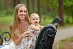La madre e la figlia bionde snelle che si siedono su un banco in Immagini Stock Libere da Diritti