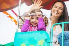 La madre e la figlia che godono della fiera di divertimento guidano, parco di divertimenti Fotografia Stock