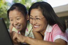 La madre e la figlia che si siedono alla tavola del cortile facendo uso del computer portatile si chiudono insieme su Immagini Stock