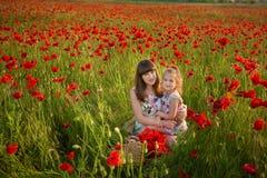 La madre e la figlia che sorridono in un papavero sistemano Il picnic nel campo del papavero Passeggiata con la famiglia nel camp Immagine Stock Libera da Diritti