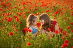 La madre e la figlia che sorridono in un papavero sistemano Il picnic nel campo del papavero Passeggiata con la famiglia nel camp Fotografie Stock Libere da Diritti