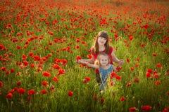 La madre e la figlia che sorridono in un papavero sistemano Il picnic nel campo del papavero Passeggiata con la famiglia nel camp Immagine Stock