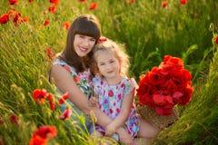 La madre e la figlia che sorridono in un papavero sistemano Il picnic nel campo del papavero Passeggiata con la famiglia nel camp Immagini Stock