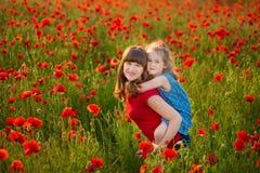 La madre e la figlia che sorridono in un papavero sistemano Il picnic nel campo del papavero Passeggiata con la famiglia nel camp Fotografia Stock