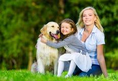 La madre e la figlia con l'animale domestico sono sull'erba verde Fotografia Stock