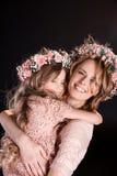 La madre e la figlia in corone floreali e nel rosa veste abbracciare Immagini Stock