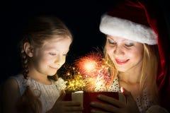 La madre e la figlia hanno aperto una scatola con un regalo Fotografie Stock