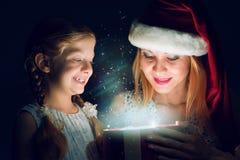 La madre e la figlia hanno aperto una scatola con un regalo Fotografia Stock