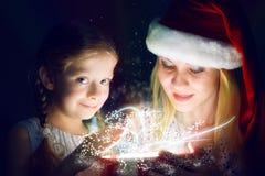 La madre e la figlia hanno aperto una scatola con un regalo Immagini Stock