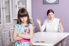 La madre e la figlia litigano a causa di esagerano il computer del telefono della compressa, la compressa, ecc immagine stock