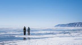 La madre e la figlia vanno sul ghiaccio blu del lago Baikal congelato Cielo blu puro Ghiaccio, colore molto piacevole Immagini Stock