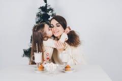 La madre e la piccola figlia bevono il cacao con le caramelle gommosa e molle Immagini Stock
