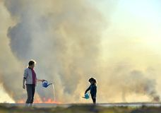 La madre e la piccola figlia estinguono il fuoco dall'annaffiatoio Fotografia Stock Libera da Diritti