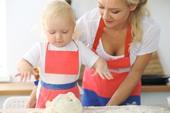 La madre e la piccola figlia stanno cucinando nella cucina Spendendo tempo tutto insieme o concetto 'nucleo familiare' felice Immagine Stock