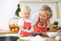 La madre e la piccola figlia stanno cucinando nella cucina Spendendo tempo tutto insieme o concetto 'nucleo familiare' felice Immagine Stock Libera da Diritti
