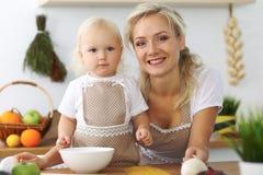 La madre e la piccola figlia stanno cucinando nella cucina Spendendo tempo tutto insieme o concetto 'nucleo familiare' felice Fotografia Stock Libera da Diritti