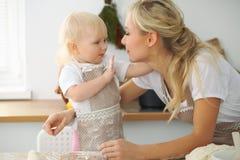 La madre e la piccola figlia stanno cucinando nella cucina Spendendo tempo tutto insieme o concetto 'nucleo familiare' felice Fotografia Stock